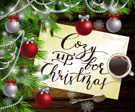 Christmas New Year design dark wooden background with christmas tree and silver and red balls and paper with handwritten Cozy up for Christmas a cup of coffee and teaspoon.