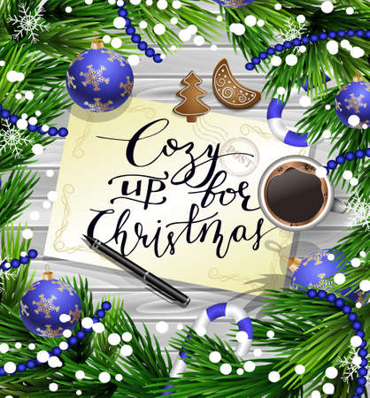 Christmas New Year design wooden background with christmas decorations candy canes snow and balls arranged in a frame with handwritten Cozy up for Christmas a cup of coffee gingerbread cookies and a pen in blue.