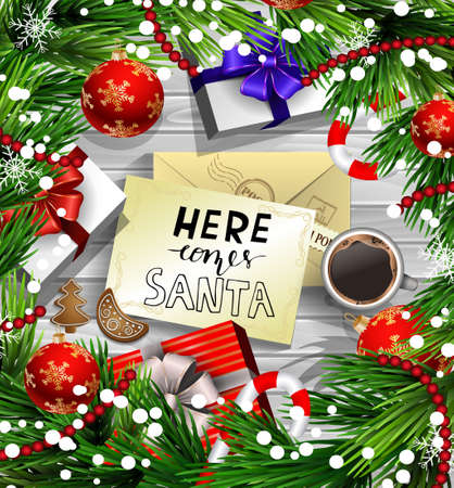 Christmas New Year design wooden background with christmas decorations candy canes snow and balls arranged in a frame with gift boxes and envelope handwritten Here comes Santa cup of coffee and gingerbread cookies. in red