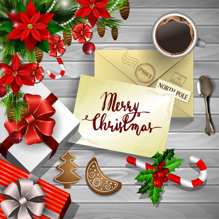 Christmas New Year design wooden background with christmas decorations candy canes with gift boxes and envelope and handwritten Merry Christmas coffee cup and gingerbread cookies and poinsettia in red.