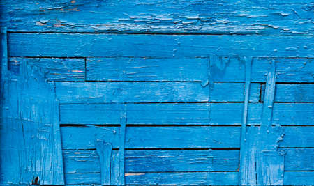Texture exfoliating cracked blue paint. Vintage wooden background with horizontal boards, with blue paint. Copy space concept.