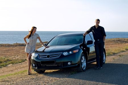 A happy family beside their new kind of cars Stock Photo