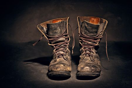 old soldiers boots worn with scratches and untied shoelaces on white background Stock Photo