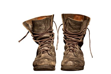 old soldiers boots worn with scratches and untied shoelaces photo