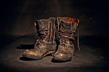 old soldier's boots worn with scratches and untied shoelaces on white background Stock Photo - 7456097