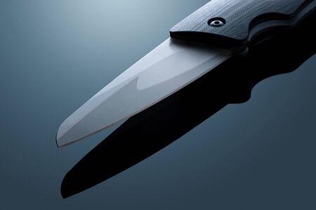 boinas: Batalla metal plegable cuchillo en el gradiente de fondo Foto de archivo
