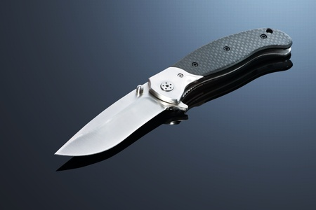 berets: Hunting metal folding knife on the background gradient