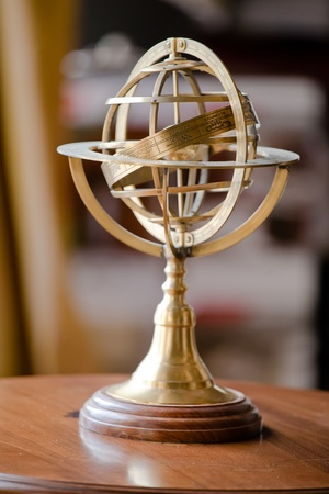 Metal armillary sphere with the signs of the zodiac on a wooden stand Stock Photo