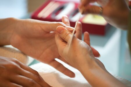 Correction and cleaning nails of wooden stick in a beauty salon manicure Stock Photo - 12636044