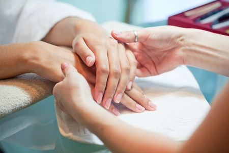 nail scissors: gentle massage of hands in the manicure beauty salon Stock Photo