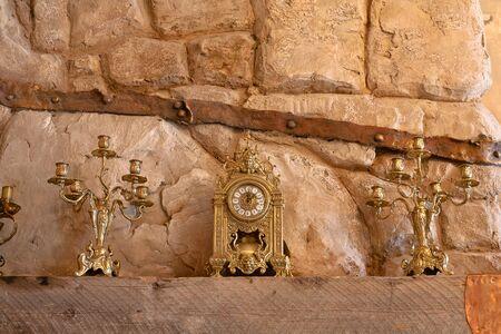 mantel: Orologio e lampadario in piedi sulla mensola del caminetto in lussuosi interni del vecchio Archivio Fotografico