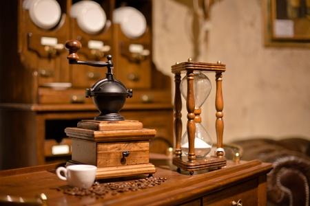 afilador: Vintage molinillo manual de madera y reloj de arena en un interior antiguo