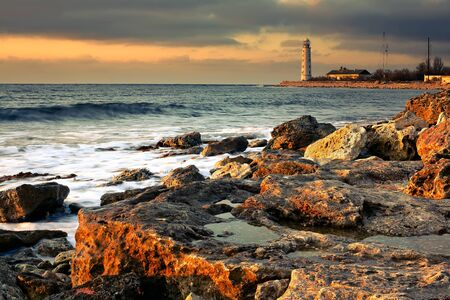 Lighthouse on the shore of the stormy sea Stock Photo - 12870676