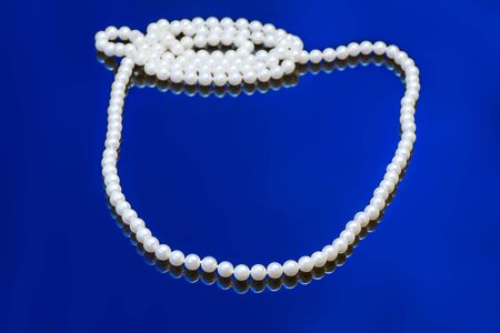 Necklace with white pearl on a blue background photo