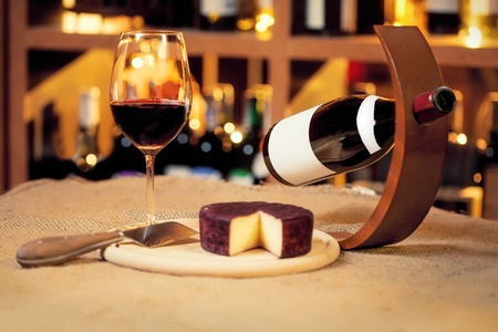 Wine and wineglass and cheese on the table photo