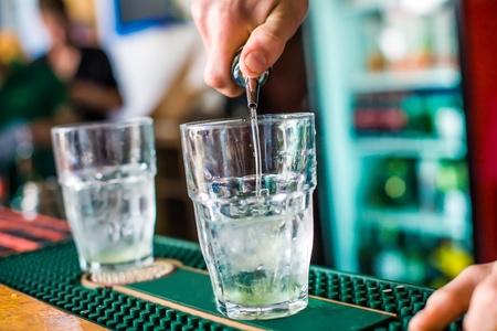 The bartender mixes a summer cocktail at the bar photo