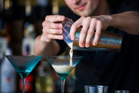 The bartender mixes a summer cocktail at the bar photo