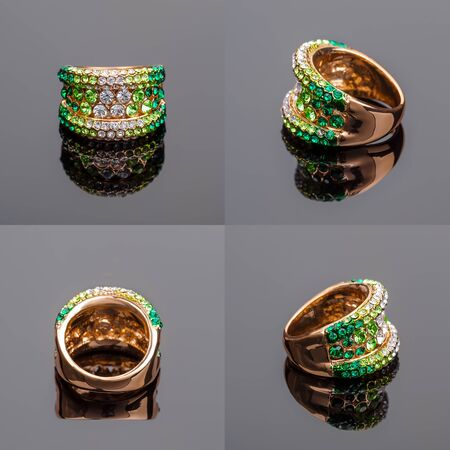 Gold ring with green crystals on a gray background photo