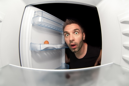 The man opened the empty refrigerator and wondered photo