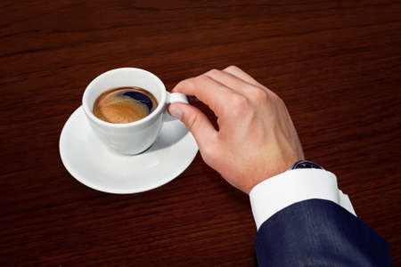Businessman hand holding a cup of coffee Stock Photo - 15647371