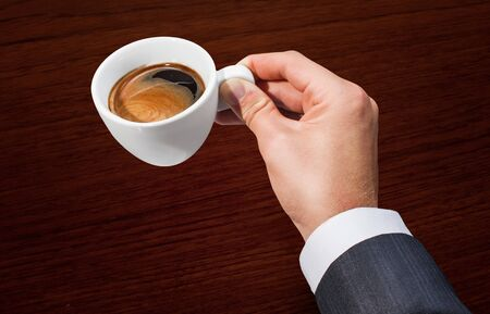 Businessman hand holding a cup of coffee Stock Photo - 15647369