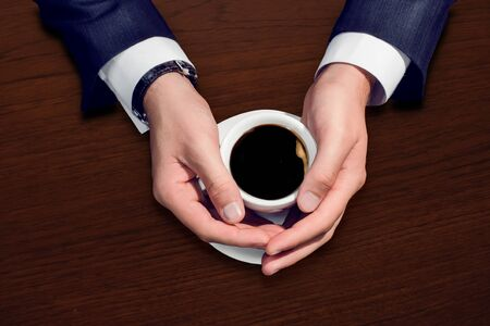 Businessman hand holding a cup of coffee photo