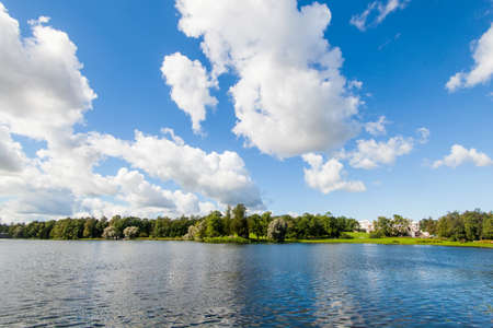 Russian palace: View of lake in Royal Catherine park located in Pushkin, Saint Petersburg. The building of Queen Catherines Palace on sunny day. Russian royal tourist attractions.