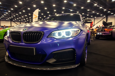 SAINT-PETERSBURG, RUSSIA - JULE 23, 2017: Front view of BMW M2 with sport tuning on Royal Auto Show. Close up of Car hood and radiator with swith on headlamp.