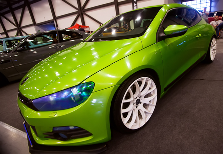 SAINT-PETERSBURG, RUSSIA - JULE 23, 2017: Front view of green car Wolkswagen with sport tuning on Royal Auto Show. Close up of Car hood and white wheel. Editorial