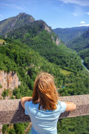 rear view of lonely girl looking on canyon on Djurdjevica Tara Bridge, Montenegro