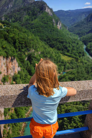 rear view of lonely girl looking on canyon on Djurdjevica Tara Bridge, Montenegro. Durmitor reserve. Stock Photo
