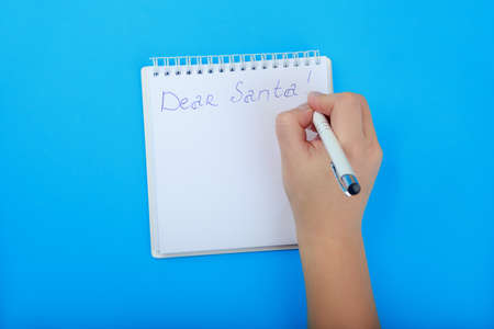 letter to Santa Claus in Notepad with space for list. childrens hand writing a letter to Santa on blue background top view Stock Photo