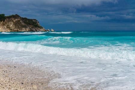 Caribbean pebble beach. Caribs. turquoise stormy sea Фото со стока