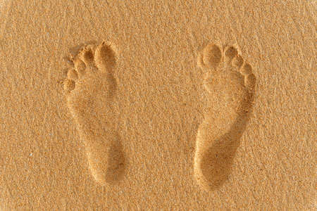 foot prints or traces of two human feet on the sand. vacation concept