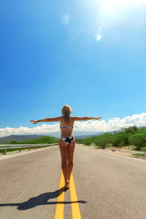 girl in bikini back view walking on asphalt road in sunny day. Travel concept, way to paradise