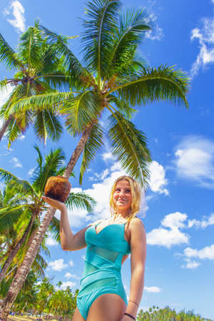 Girl holding the coconut under the palm tree on the beach