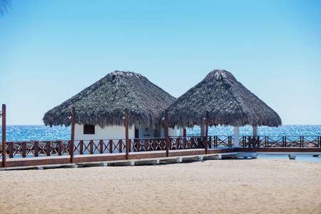 small house with a thatched roof over the sea. Luxury bungalows on the beach