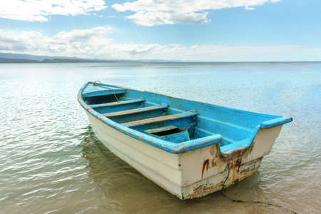 empty old wooden white blue boat on shallow water