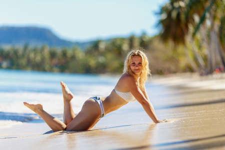 slim sexy blonde girl  model in bikini on a tropical beach 스톡 콘텐츠