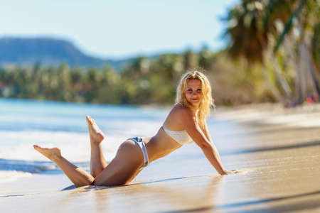 slim sexy blonde girl  model in bikini on a tropical beach Foto de archivo
