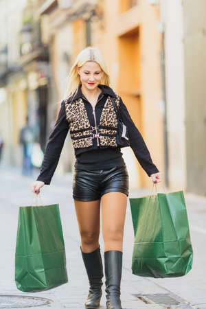 Happy Beautiful young blonde girl holding two green paper packages walking on Shopping europian street
