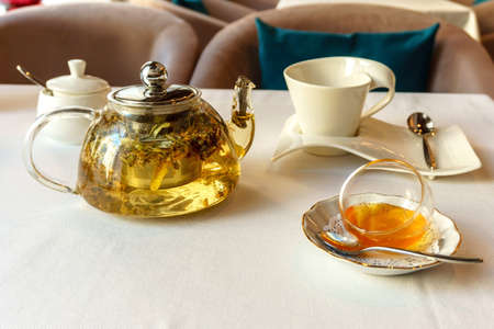 Breakfast in the cafe, full teapot with green tea and bowl of honey on the table