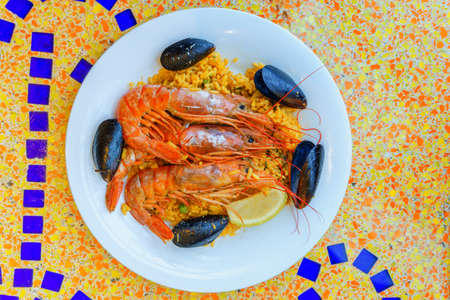 sea food, paella portion, rice with tiger shrimps, mussels and lemon Standard-Bild