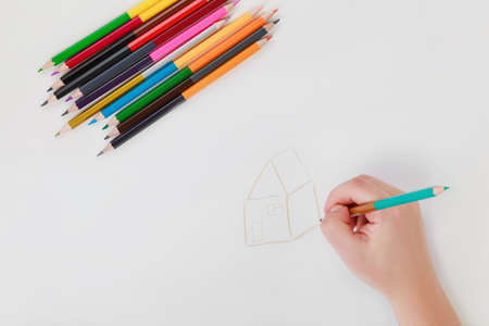 hand drawing with color double-sided pencils on white background, female hand drawing the house