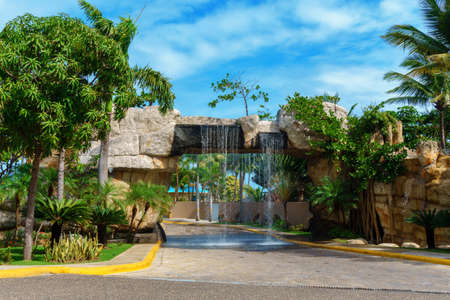 artificial waterfall above the road, interesting entrance to the park. Puerto Plata, Dominican Republic 스톡 콘텐츠