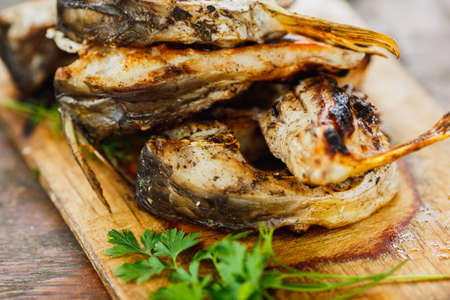 yammy grilled fish pieces with parsley on the wooden board