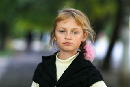 harmful child, disgruntled little girl on blured background