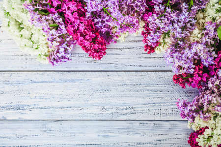 Fresh lilac flowers on the wooden vintage background