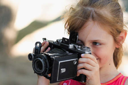 little girl kid photographer holding old vintage photocamera Stock Photo