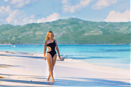 young beautiful girl in black swimwear in full growth walking on the blue beach